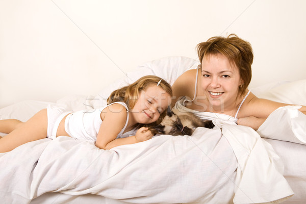 Little girl and her mother caressing their kitten Stock photo © ilona75