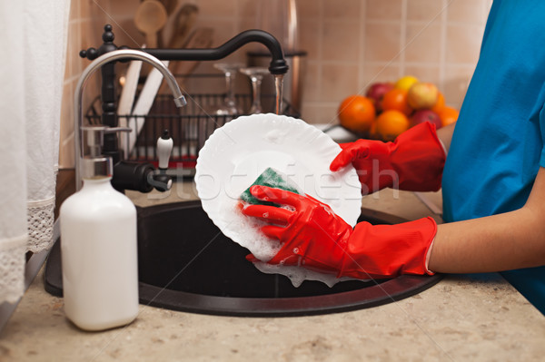 Washing the dishes after a meal - child hands scrubbing a plate  Stock photo © ilona75