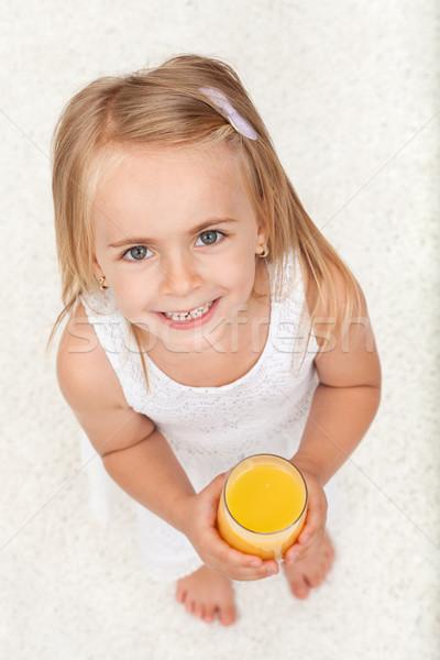 Little happy girl having a glass of fruit juice - top view Stock photo © ilona75