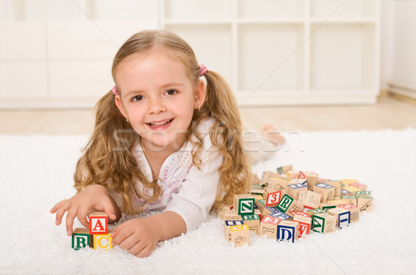 Stock photo: Little girl with alphabet wooden blocks playing