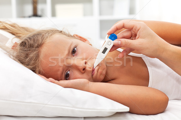 Sick little girl with thermometer laying in bed Stock photo © ilona75