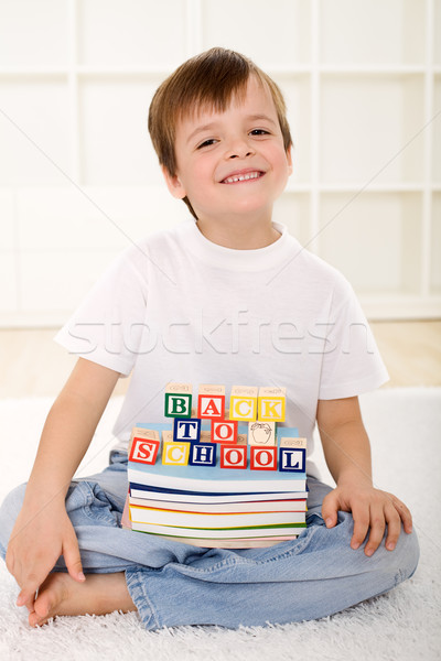 Stock photo: Happy kid with school books sitting on the floor