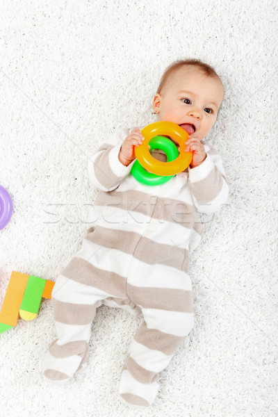Baby girl playing on the floor chewing toys Stock photo © ilona75