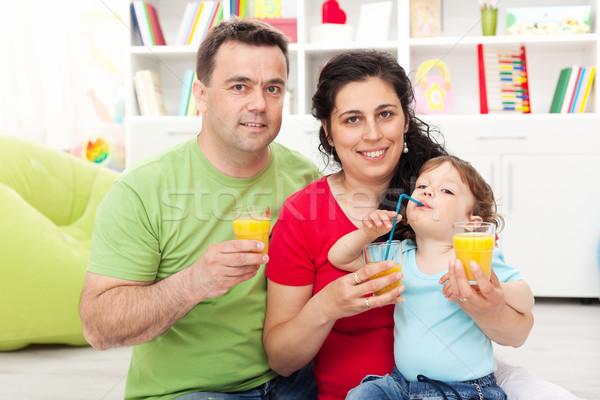 Family with child having fruit juice Stock photo © ilona75