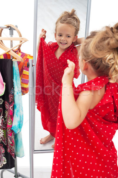Happy little girl trying on dresses in front of mirror Stock photo © ilona75