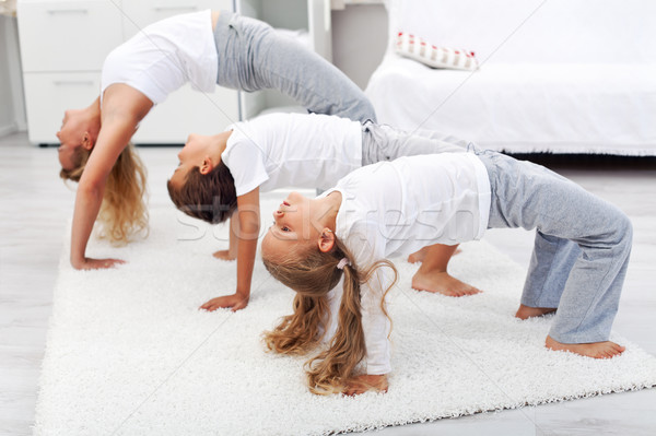 Woman and kids doing gymnastic exercises at home Stock photo © ilona75