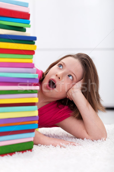 Young school girl shocked by the large stack of books Stock photo © ilona75