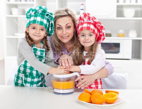 Woman and kids making fresh fruit juice Stock photo © ilona75