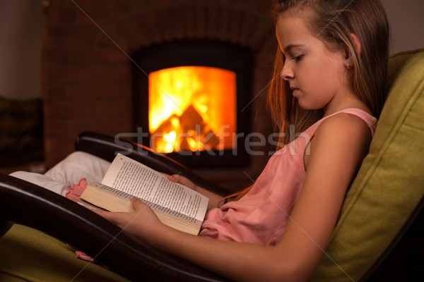Fiatal lány fotel olvas kandalló este lány Stock fotó © ilona75