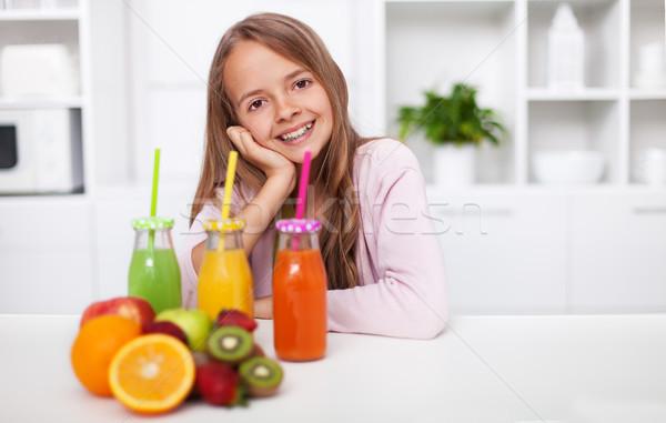 Young teenager girl preparing fresh fruit juice in the kitchen Stock photo © ilona75