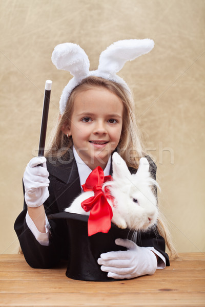 Happy magician girl with white bunny in a hat Stock photo © ilona75