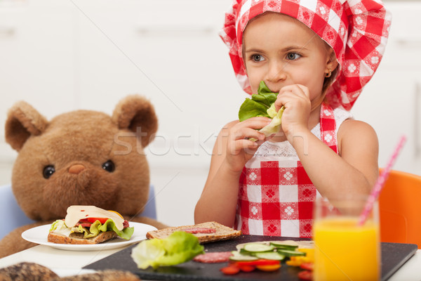 Stock photo: Little girl playing and having a healthy snack with her teddy be
