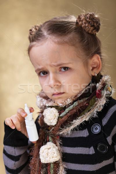 Little girl having a cold holding a nose spray Stock photo © ilona75