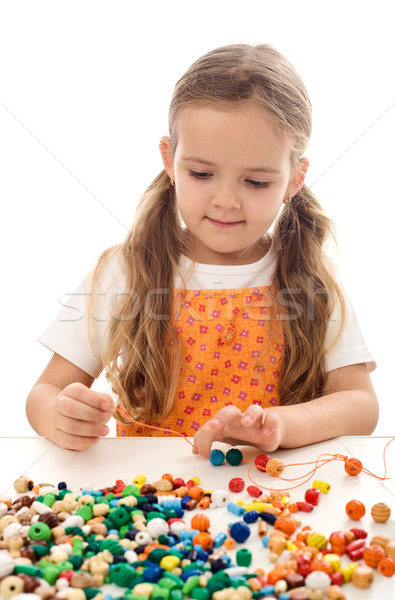 Little girl playing with string and beads Stock photo © ilona75