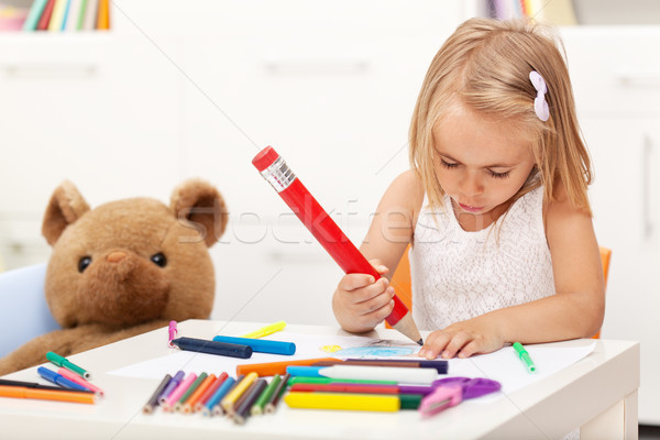 Little girl drawing with a large pencil - sitting at the table Stock photo © ilona75