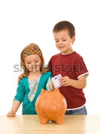 Kids saving coins in large piggy bank Stock photo © ilona75