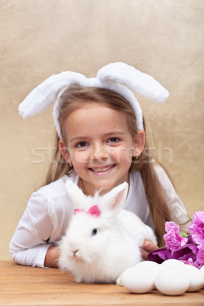 Happy little girl with bunny ears and her cute white rabbit Stock photo © ilona75