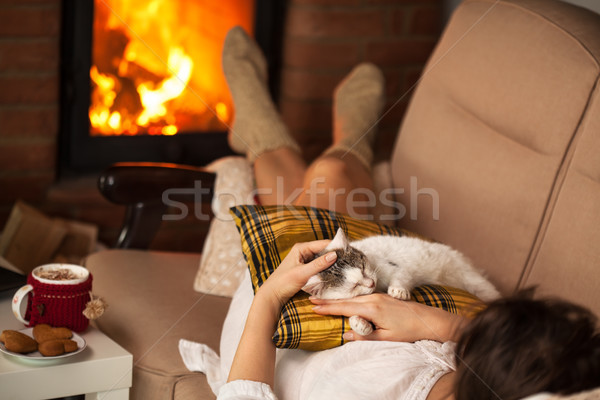 Woman enjoying the fire and some fine company - her kitten Stock photo © ilona75