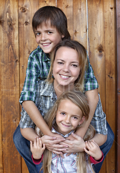Happy family portrait against wooden wall Stock photo © ilona75