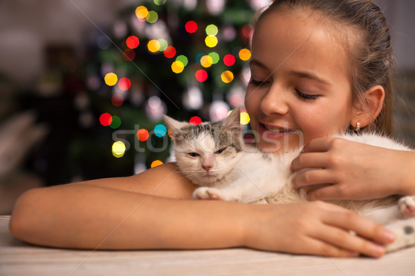 Young girl with her rescued kitten in front of the xmas tree at  Stock photo © ilona75