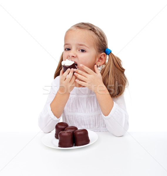 Küçük kız yeme kremsi çikolata tatlı el Stok fotoğraf © ilona75
