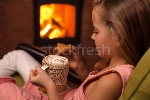 Fiatal lány ül kandalló forró csokoládé sütik pihenés Stock fotó © ilona75