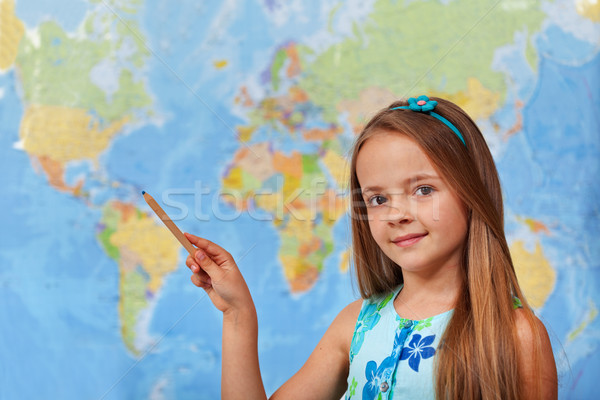 Little student girl pointing to blurry world map Stock photo © ilona75
