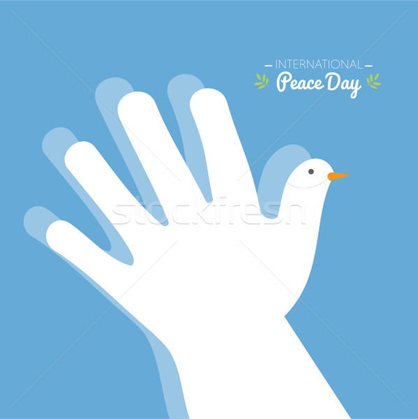 International peace day with hand making the shape of a dove on a blue sky background Stock photo © Imaagio