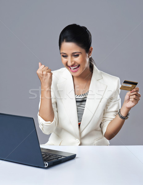 Stock photo: Businesswoman looking excited while doing online shopping with a laptop