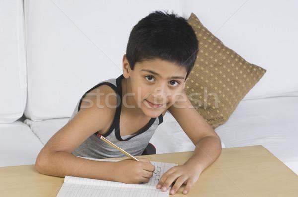 Portret chłopca posiedzenia sofa piśmie student Zdjęcia stock © imagedb