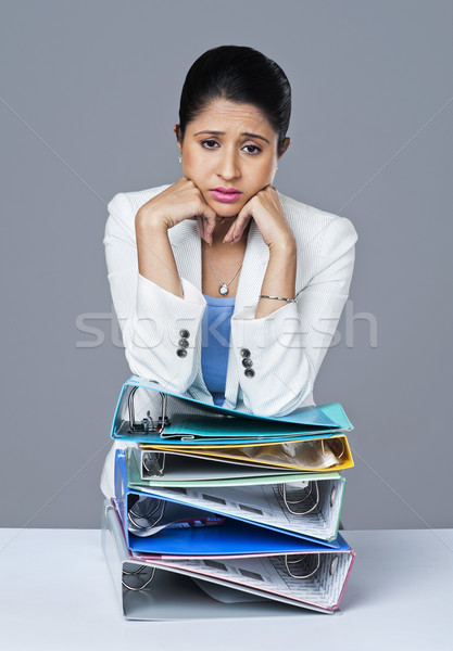 Businesswoman leaning on a stack of files and looking worried Stock photo © imagedb