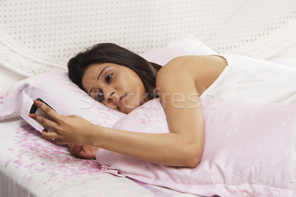 Woman lying on the bed and holding a mobile phone Stock photo © imagedb
