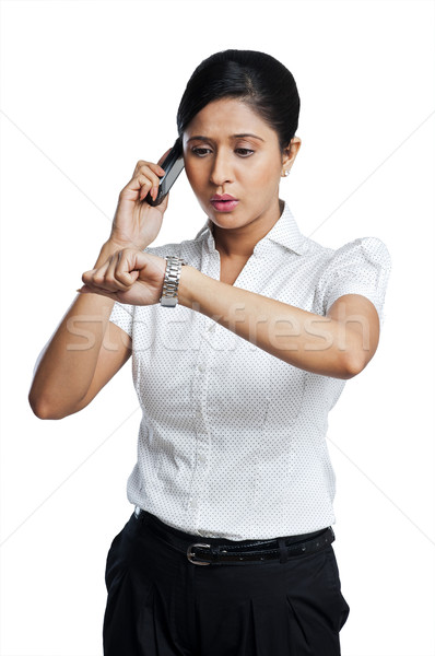 Businesswoman checking the time while talking on a mobile phone Stock photo © imagedb