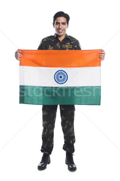 Portrait of an army soldier holding Indian flag and smiling Stock photo © imagedb