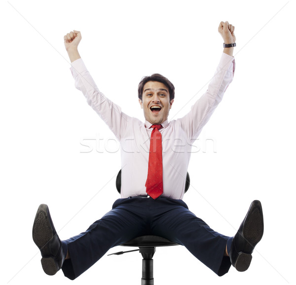 Businessman sitting on an office chair and looking excited Stock photo © imagedb