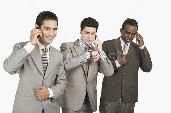 Három üzletemberek beszél mobiltelefonok üzlet kommunikáció Stock fotó © imagedb