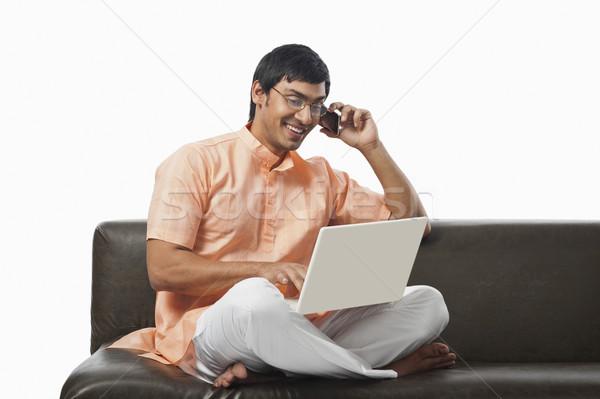 Férfi laptopot használ beszél mobiltelefon kanapé laptop Stock fotó © imagedb