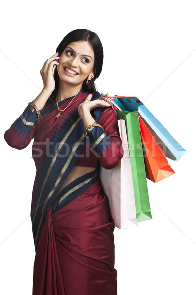 Stock photo: Traditionally Indian woman talking on a cell phone with shopping bags