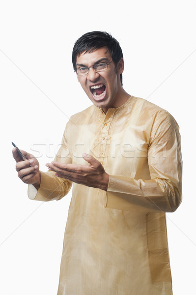 Bengali man text messaging on a mobile phone and shouting Stock photo © imagedb