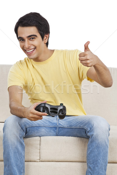 Man showing thumbs up sign while playing a video game Stock photo © imagedb