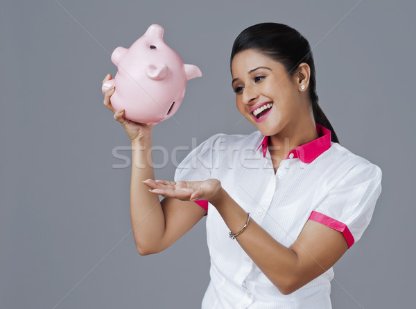 Woman withdrawing money from piggy bank Stock photo © imagedb