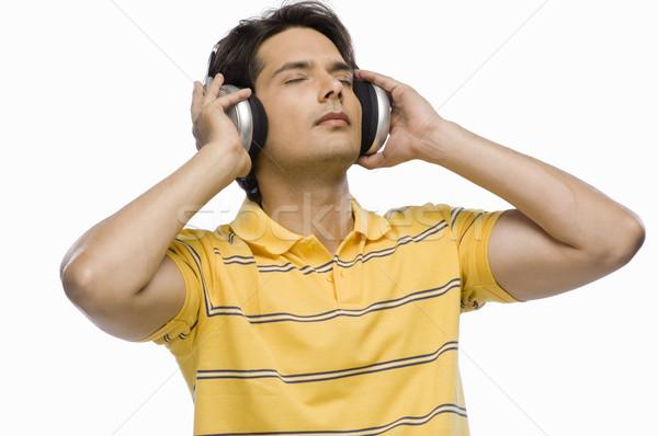 Joven escuchar música música hombre moderna amarillo Foto stock © imagedb