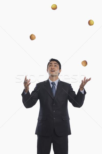 Empresário malabarismo maçãs negócio homem diversão Foto stock © imagedb