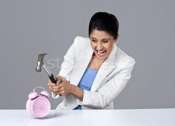 Businesswoman smashing alarm clock with hammer Stock photo © imagedb