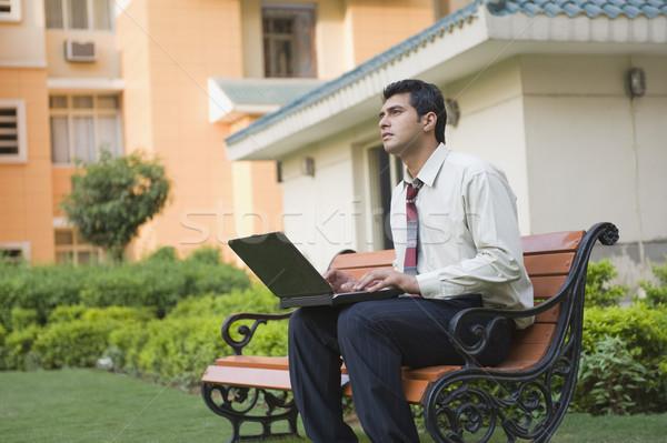 Empresario sesión banco usando la computadora portátil negocios hombre Foto stock © imagedb