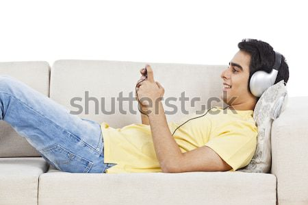 Man lying on a couch and listening to music on a mobile phone Stock photo © imagedb