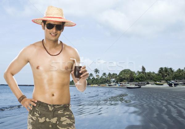 Młody człowiek szkła napój bezalkoholowy plaży Zdjęcia stock © imagedb