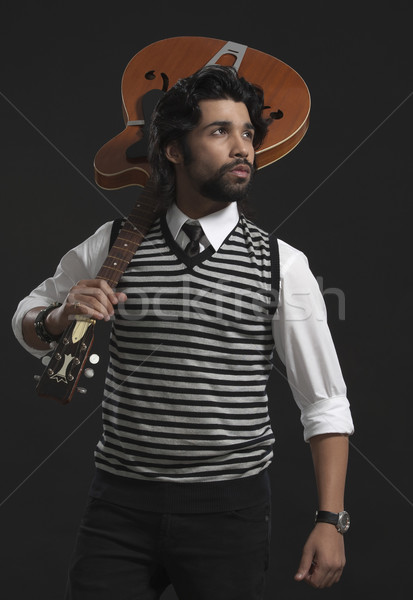 Musician holding a guitar and thinking Stock photo © imagedb