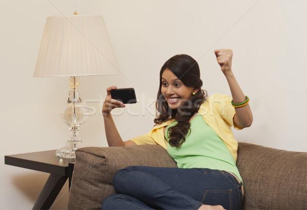 Nő sms üzenetküldés mobiltelefon farmer siker ököl Stock fotó © imagedb