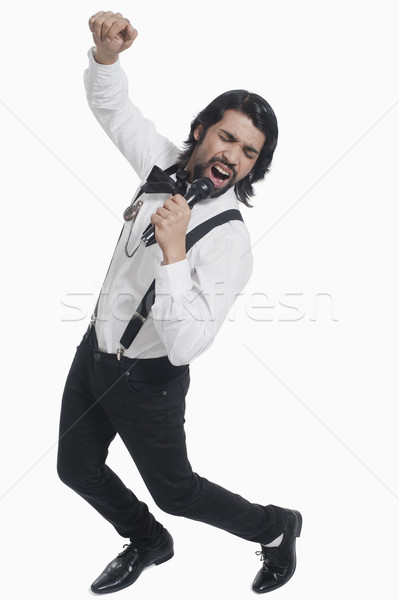 Singer holding a mike and singing Stock photo © imagedb